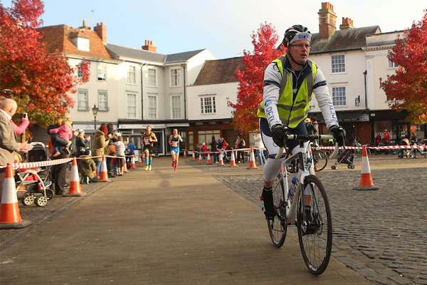 One of our cyclists leading the runners across Abingdon town square. © SussexSportPhotography